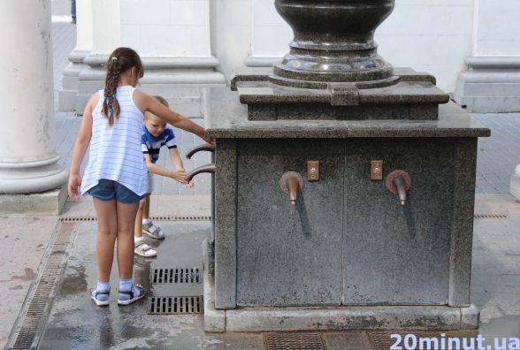 Тернополяни рятуються від спеки водою з бювету біля Катедри