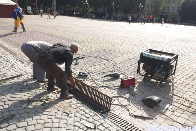 Фото дня: на Театралці чистять водостоки та кладуть нову бруківку