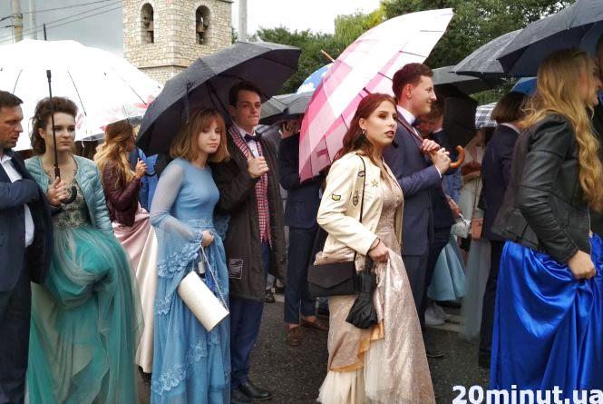 У пальтах та куртках вийшли випускники на урочистий парад містом (оновлене)