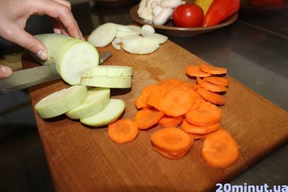 Накраяти кабачок, цибулю і моркву кружальцями, викласти до смаженого м'яса