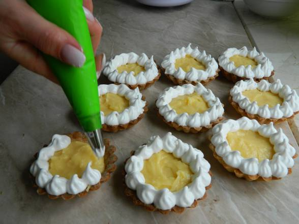 Начинити тарталетки лимонним курдом, прикрасити меренгами за допомогою кондитерського шприца