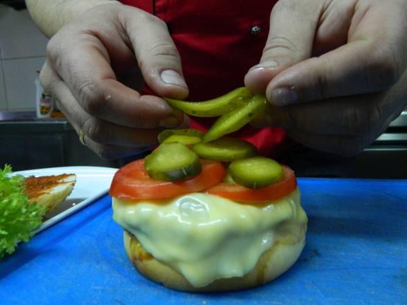 Покласти на сир тонкі скибки свіжого помідора та солоного огірка