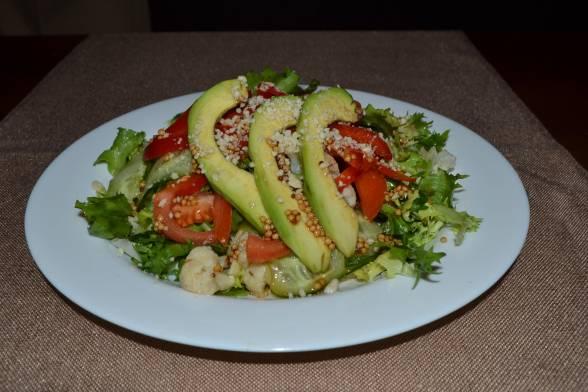 Прикрасити салат смужками авокадо, посипати подрібненими горішками