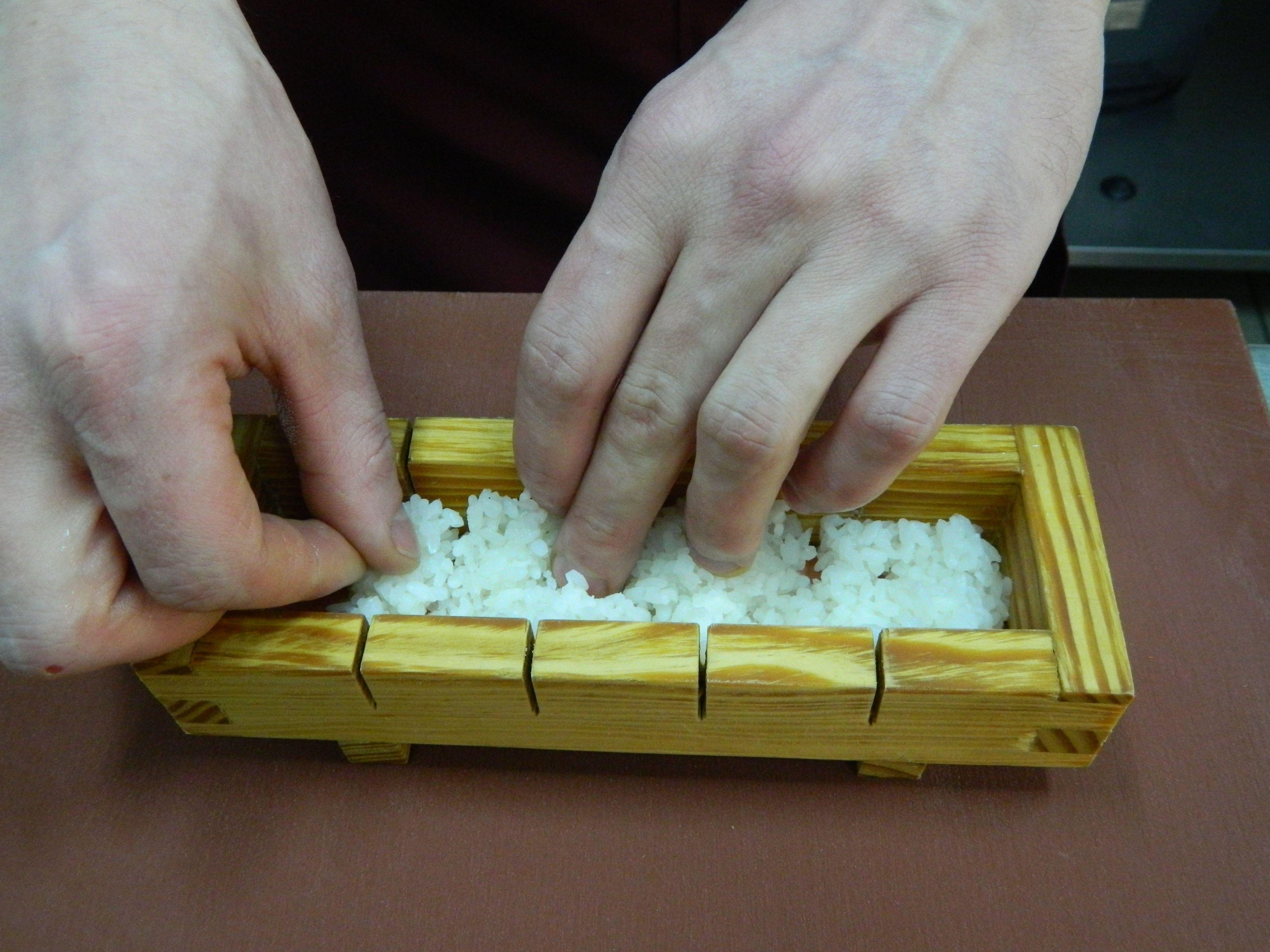 У прес покласти соєвий папір, на нього — половину вареного рису, втрамбувати