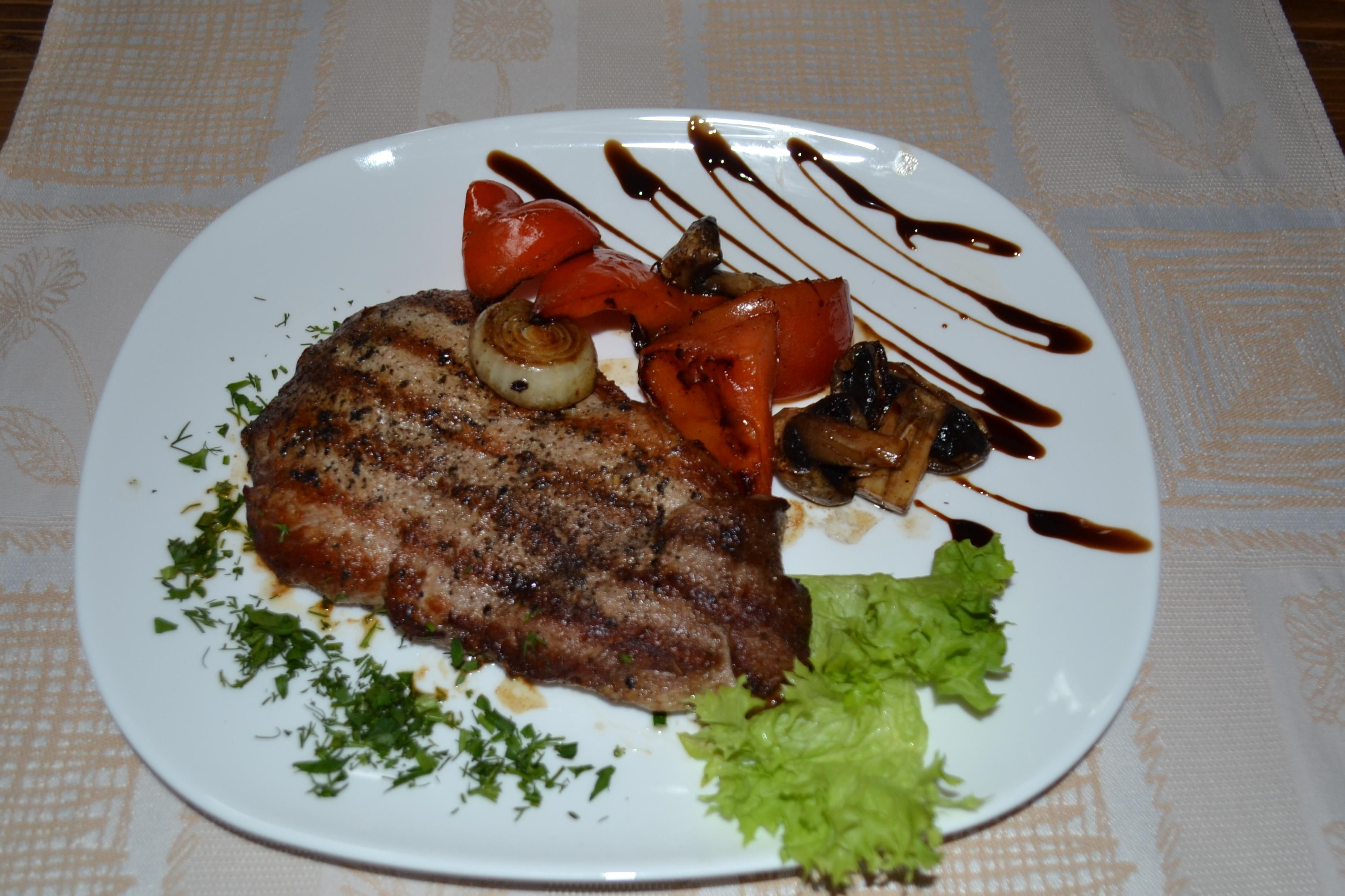 Викласти стейк з овочами на тарілку, прикрасити страву заленню
