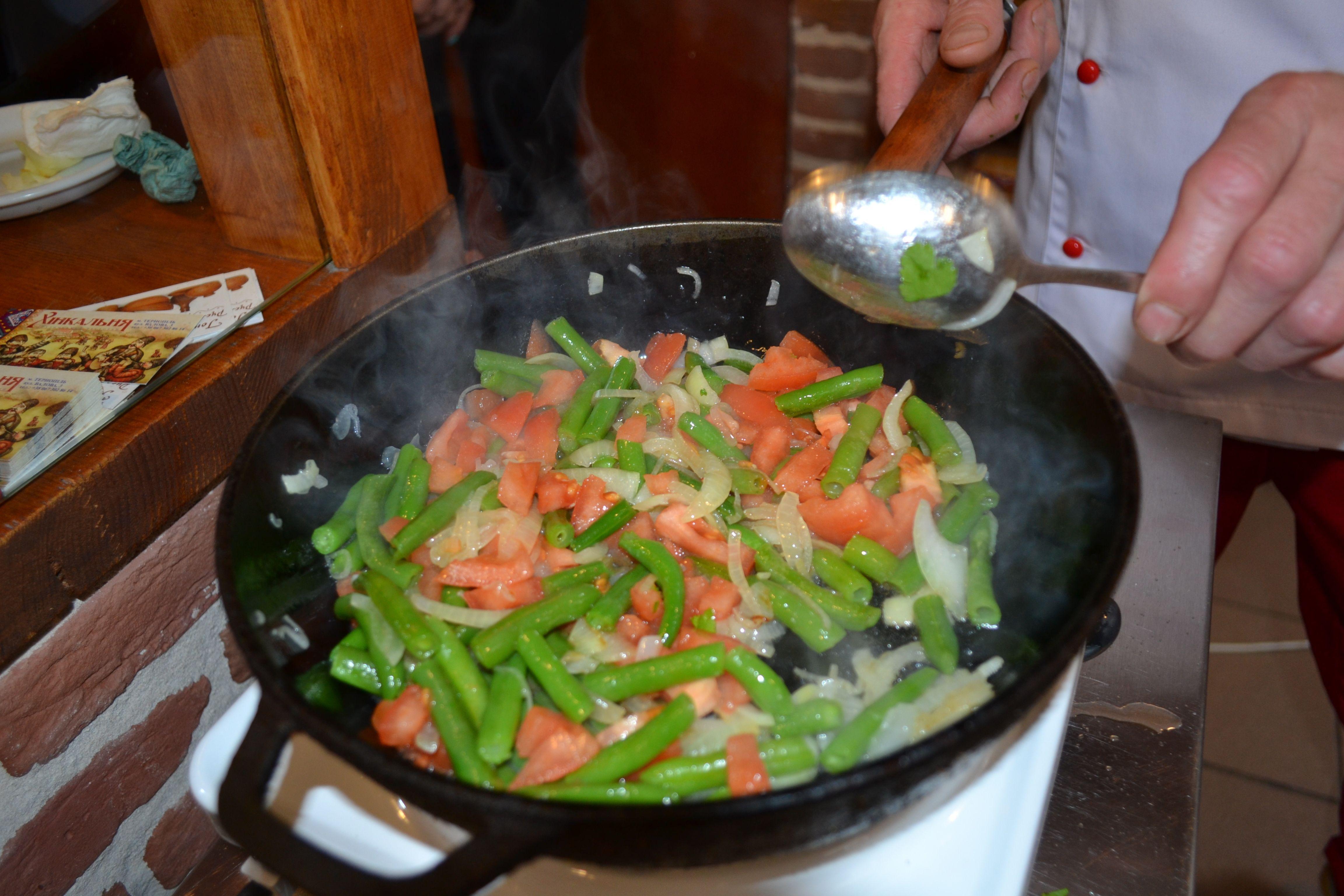 До тушкованої квасолі додати помідор, спеції і подрібнену кінзу